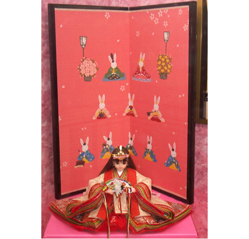 Licca Doll with rabbit-printed screen, Tokyo, Japan. Girl Museum, 2010. Licca, Japan's Barbie doll, dresses in her hina costume every year, shown here in a shop display.