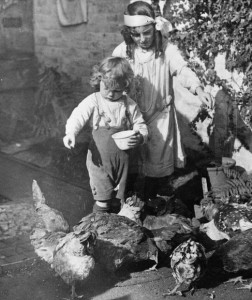 Young children feed chickens on a British farm during the World War One. Image via BBC.
