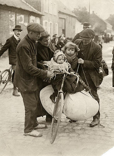 Man holding a heavy loaded bicycle in balance, two children and a large bundle of clothing on it, a woman and and other man helping. The children warmly dressed. Refugees from Antwerp. Belgium, 1914, Nationaal Archief.