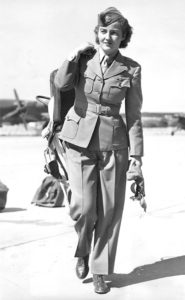 American pilot and Commander of the Women's Auxiliary Ferrying Squadron (or WAFS, which was later absorbed into the WASP) Nancy Harkness Love (1914 - 1976) carries her helmet, goggles, and parachute as she walks across the tarmac of an unidentified airfield in England, September 1942. Photo by PhotoQuest/Getty Images.