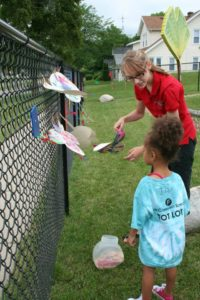 Hillary helping local students create beautiful butterfly paintings.