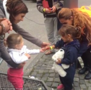 A German toddler shares her sweets with a Syrian refugee. Image from Cassandra Vinograd/Vine.