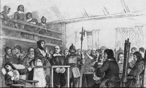 Awoman in handcuff on trial for witchcraft.