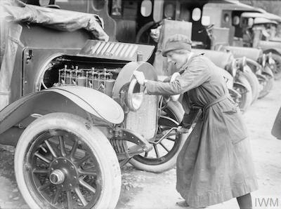 A member of the British Red Cross Society, Voluntary Aid Detachment (VAD) starts up the engine of her ambulance, Etaples, 27 June 1917. Copyright: IWM (Q 2446).