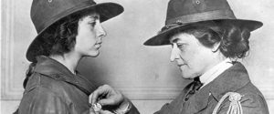 Juliette Gordon Low, founder of Girl Scouts, pinning a badge on a scout.