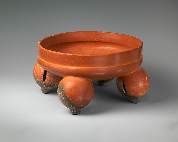 Red bowl standing on four round pods with slits
