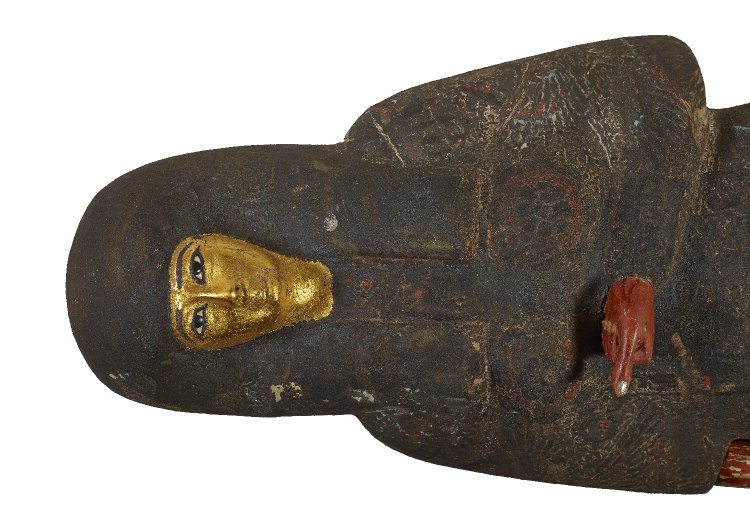 Mummy case of a young girl, obliterated by a coating of black resin. Only the face and hands are visible, with the face made of gold and the arms of wood.