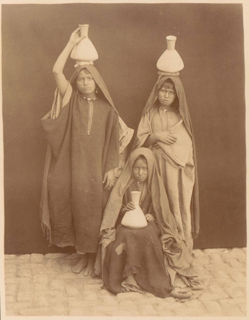 Three young Arab girls hold water jugs and pose for a photograph.