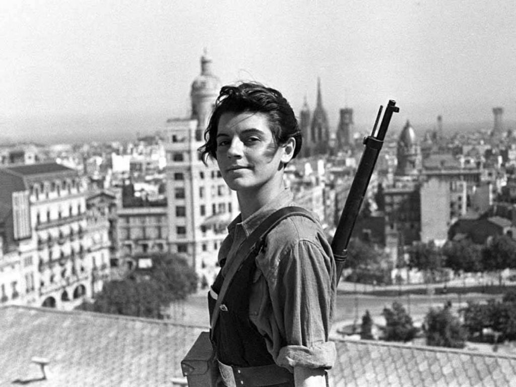 Marina Ginestà holds a rifle and smiles on a rooftop in Barcelona in July 1936