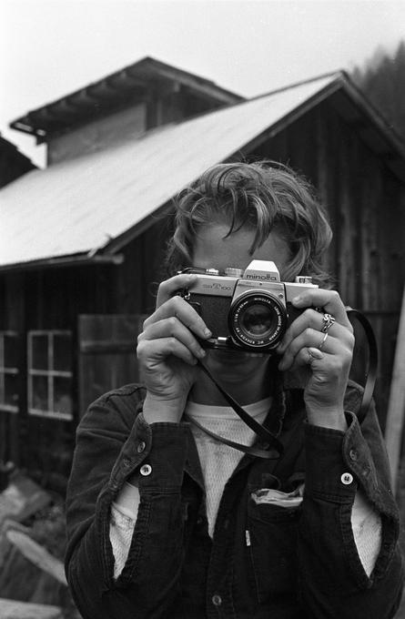 Woman looking at photographer holding a camera