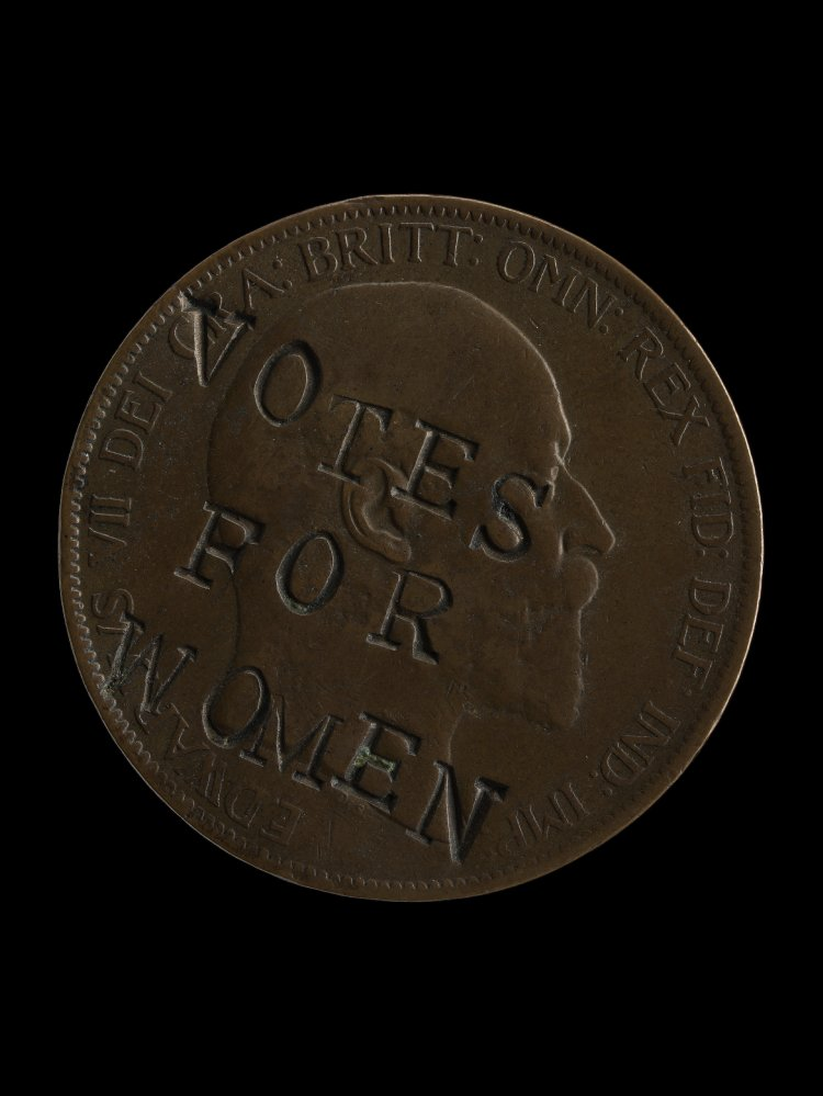 """British coin defaced by suffragettes, stamped with the phrase """"Votes for Women"""" in 1903."""