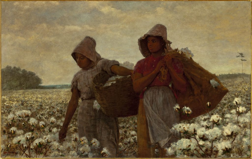 Two African American girls standing in a field of cotton, holding sacks and looking out across the landscape.
