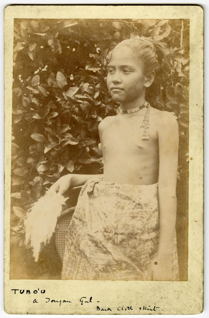 A young girl, Tubo'u, standing among trees in native dress