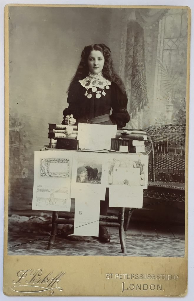 Photograph of a Victorian era school girl standing proudly with her many certificates of achievement and reward medals.