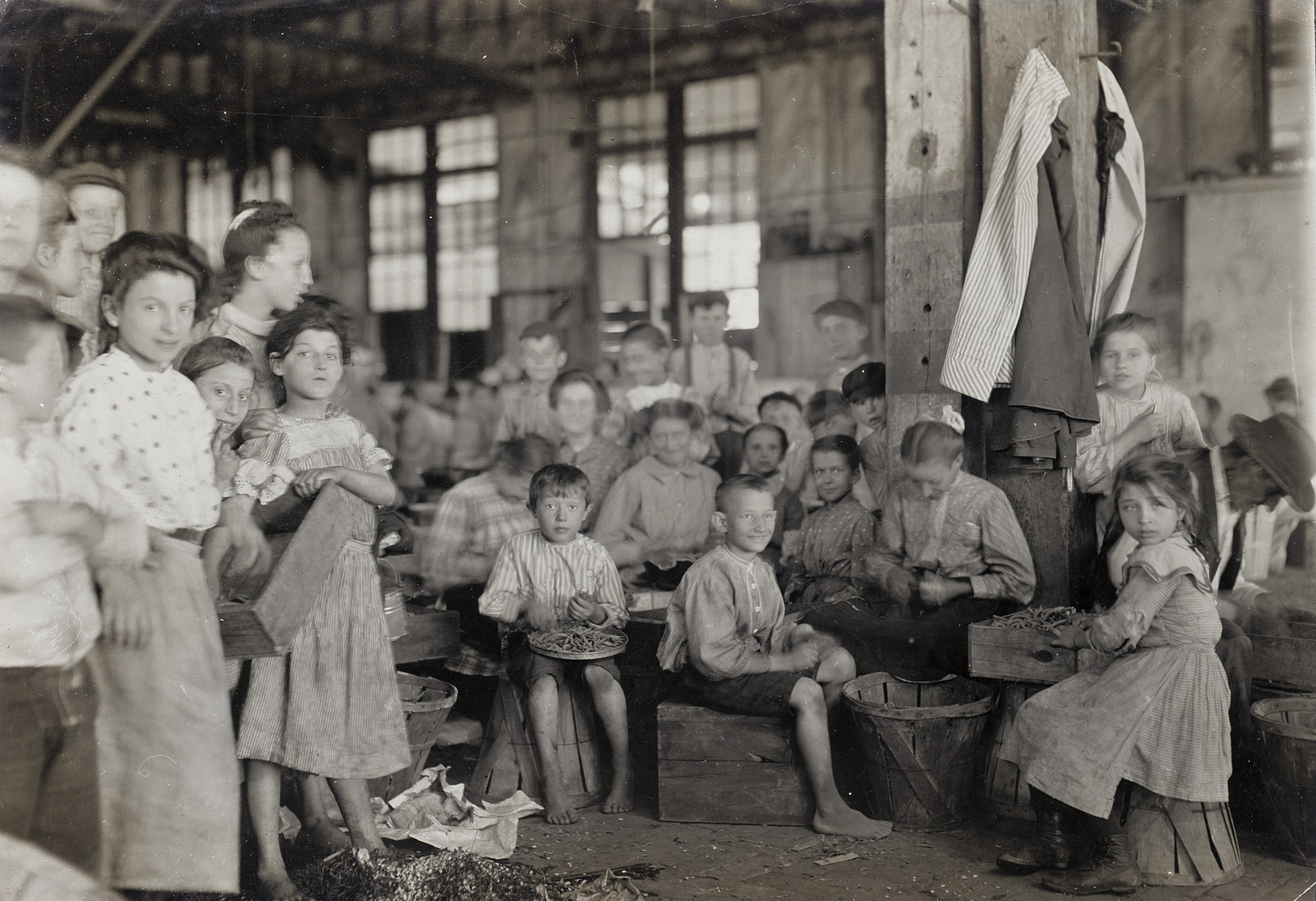 Young children in a factory pose for a group picture.