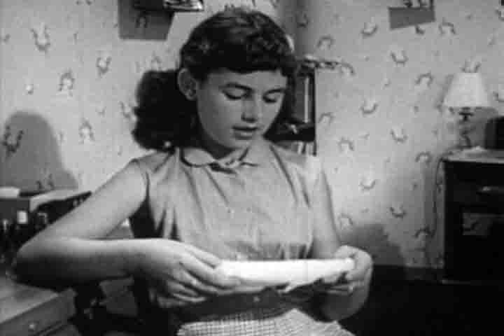 Girl looking at menstrual item.