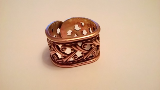 A small copper ring, handmade, with cutout designs. Nan's Copper Ring - Johannah Lord - Heirloom