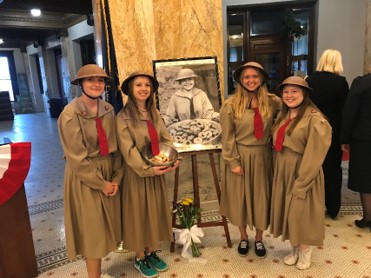 Four girls in historic costume surround a picture of Helen
