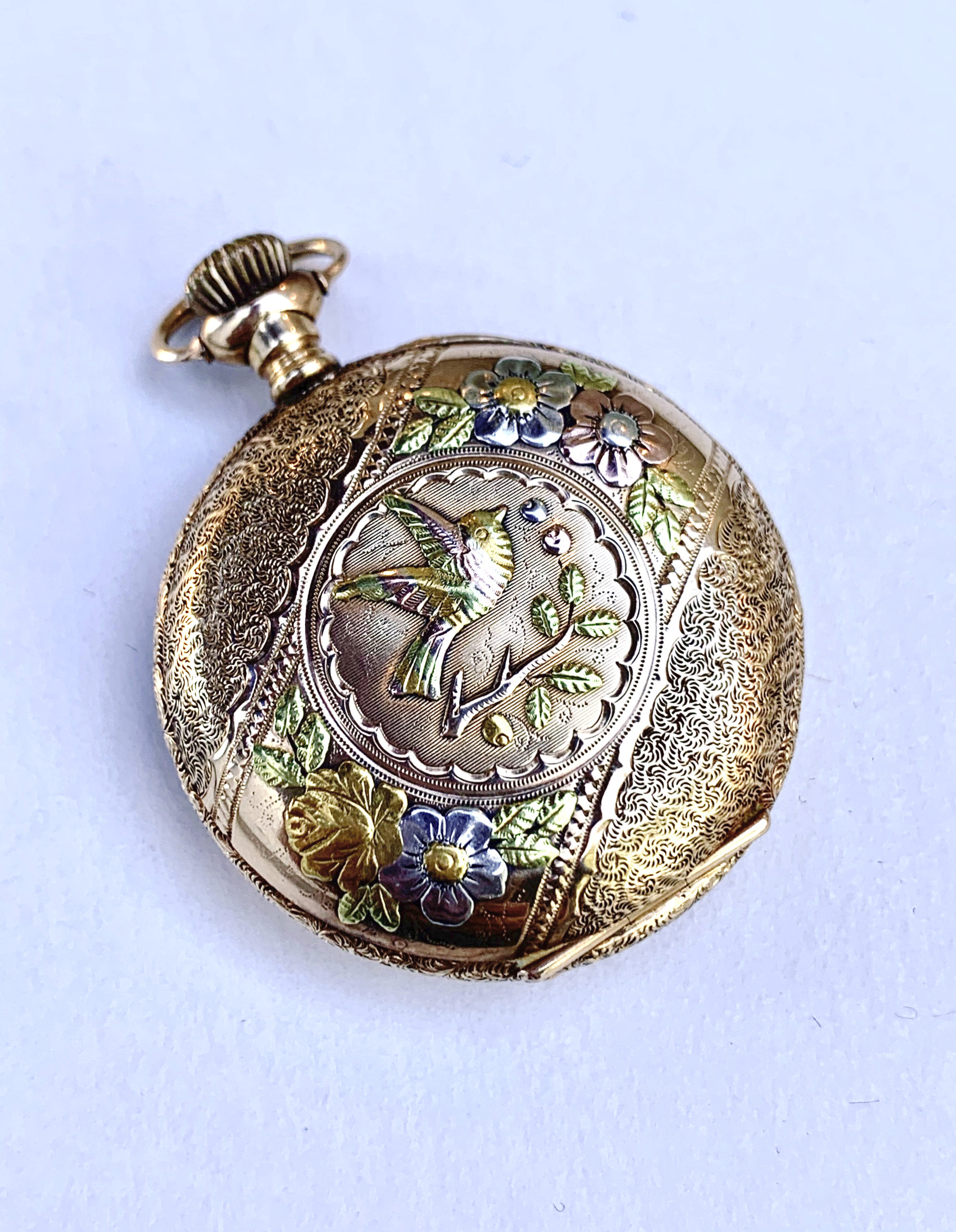Pocket watch in gold with embossed bird and twig