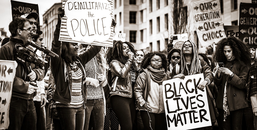 Black girls hold protest signs and speak at a rally