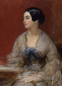 Caroline is seated, staring to the viewer's left. Her face is the only part in focus.