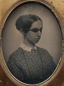 Photograph of Laura Bridgman, in a floral dress wearing goggles that black out her eyes.