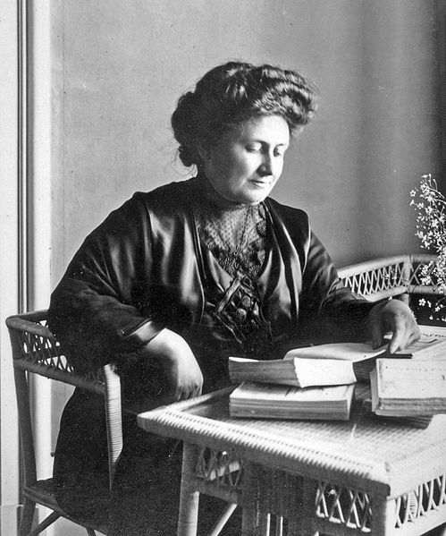Maria Montessori as an adult, sitting at a desk reading books.