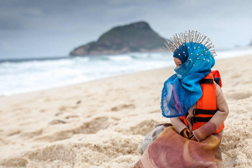 A Barbie doll dressed in a headscarf and life preserver sits on the beach, looking out to the ocean