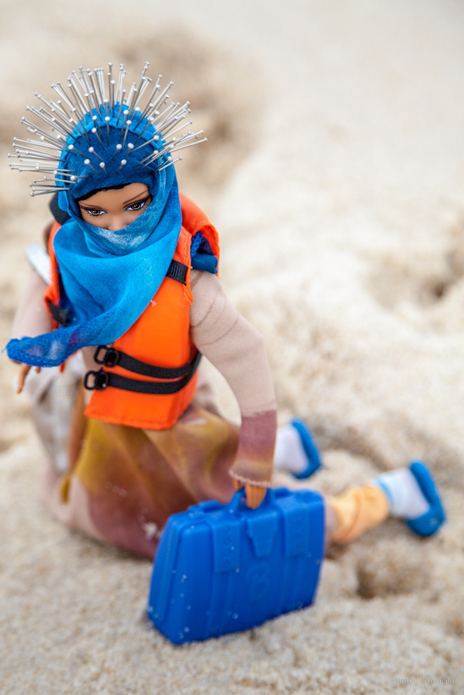 A Barbie dressed in a headscarf and life preserver holds a blue suitcase in the sand