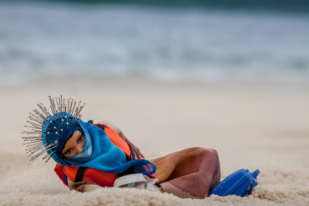 A Barbie dressed in a headscarf and life vest, holding a suitcase, lies washed up and sandy on the beach