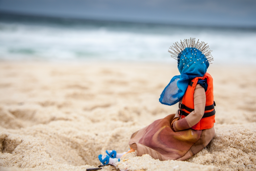 A Barbie dressed in a headscarf and life vest sits on the beach, staring at the ocean