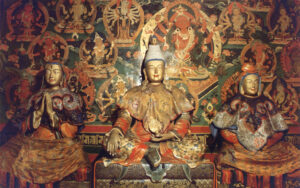 Seated figure in gold and red surrounded by depictions of women ad gods