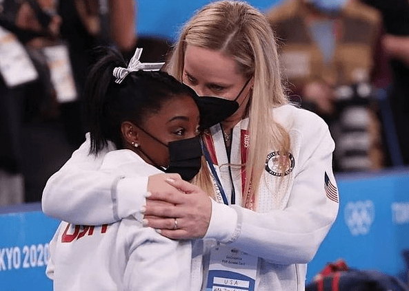 Simone Biles at left receives a hug from one of her coaches. Both women are dressed in white tracksuits and wearing face masks.